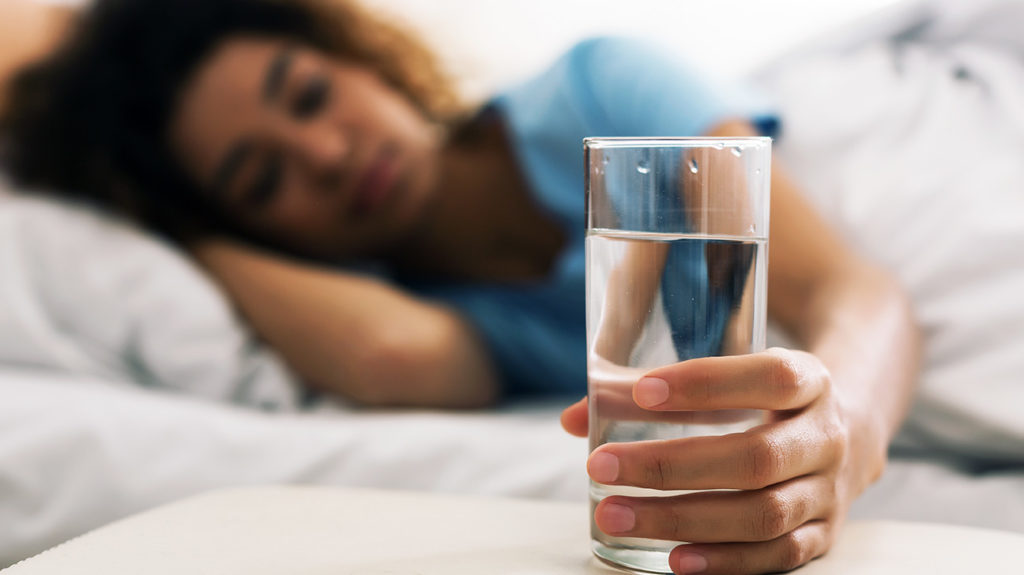 a woman reaching for a glass of water from her bed that she is going to drink as that is how to get more energy in the morning