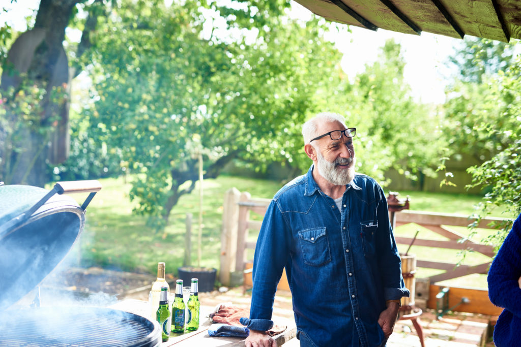 older man leaning on counter next to barbecue