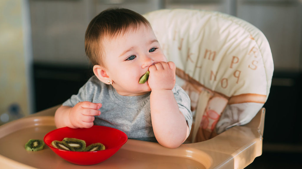 A 1-year old eats kiwi, which is a good food for a 1-year-old.