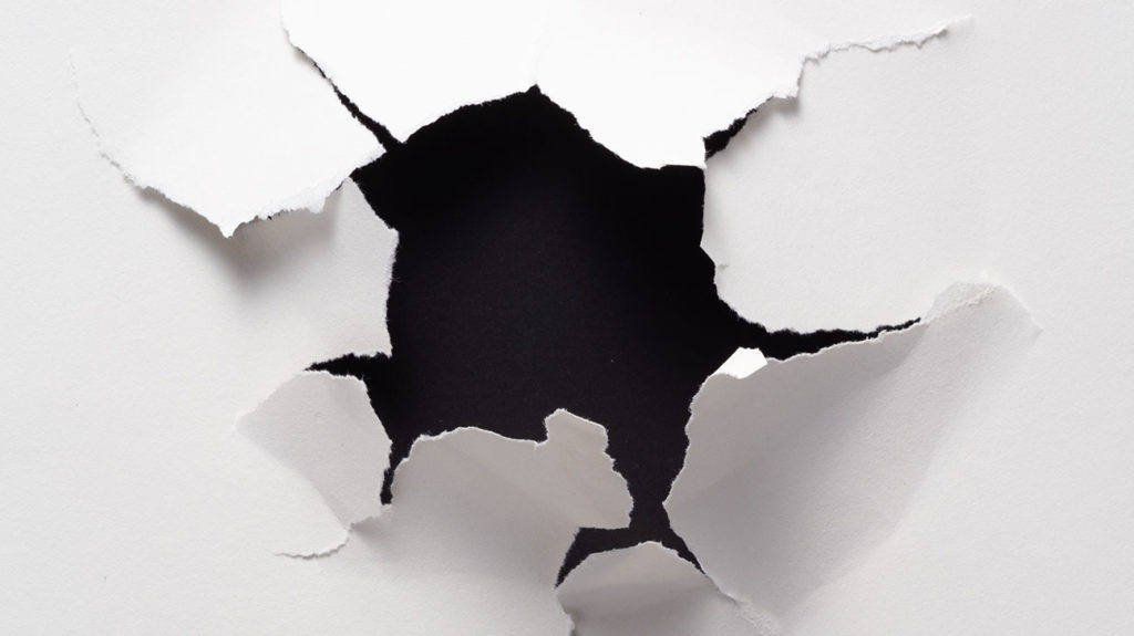 An abstract photo of white paper being broken illustrating the definition of white fragility and discomfort that may arise when confronted with racism.