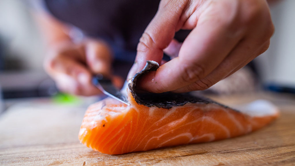 A photo of a person preparing salmon, which is one of the healthy fats for keto.