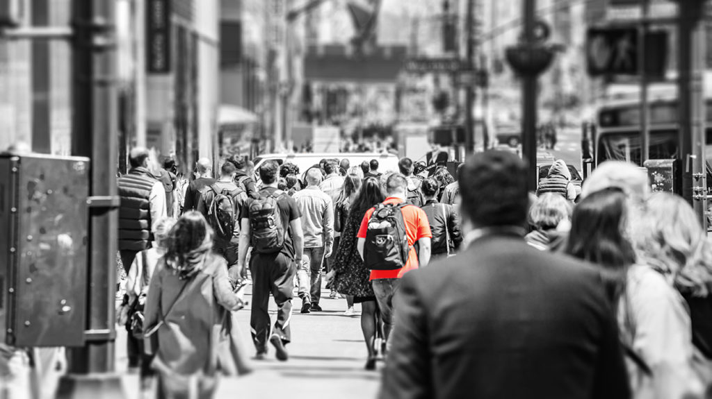 a black and white photo of a city street with one person's red t-shirt still in colour as a way to demonstrate what is contact tracing
