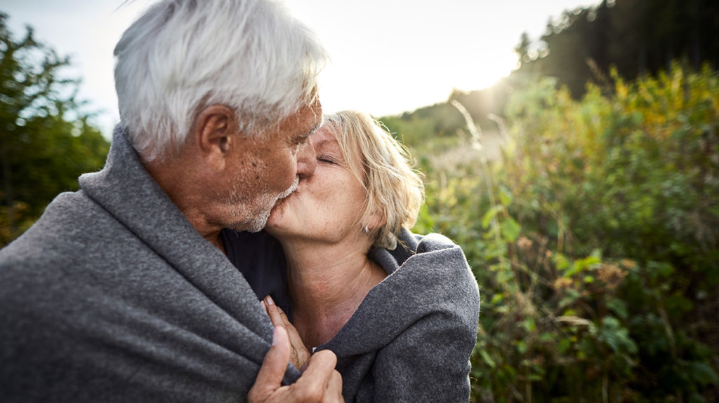 a senior couple kissing where there is not risk of spreading canker sore infections as they are not contagious