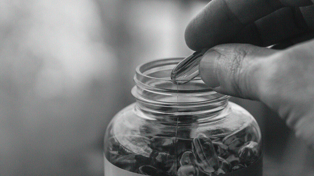 A person taking a testosterone supplement from a container.