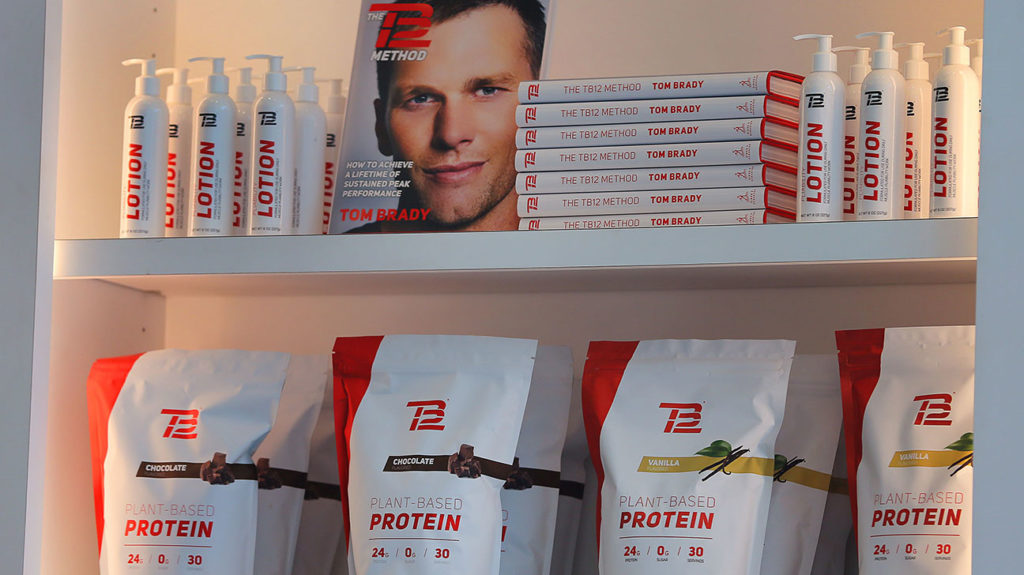 A photo from the inside of the TB12 store in Boston showing Tom Brady's book about the Tom Brady diet, protein powder, and lotion.