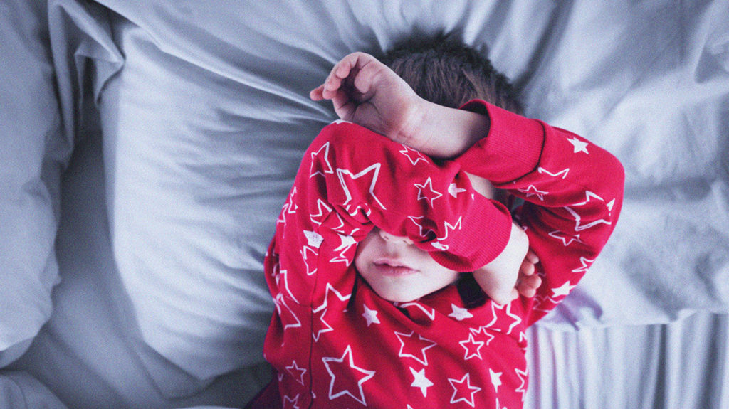 a child lying in bed and covering his eyes because of night terrors