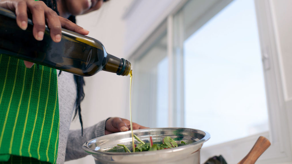 A woman adds a keto-friendly salad dressing to her salad.