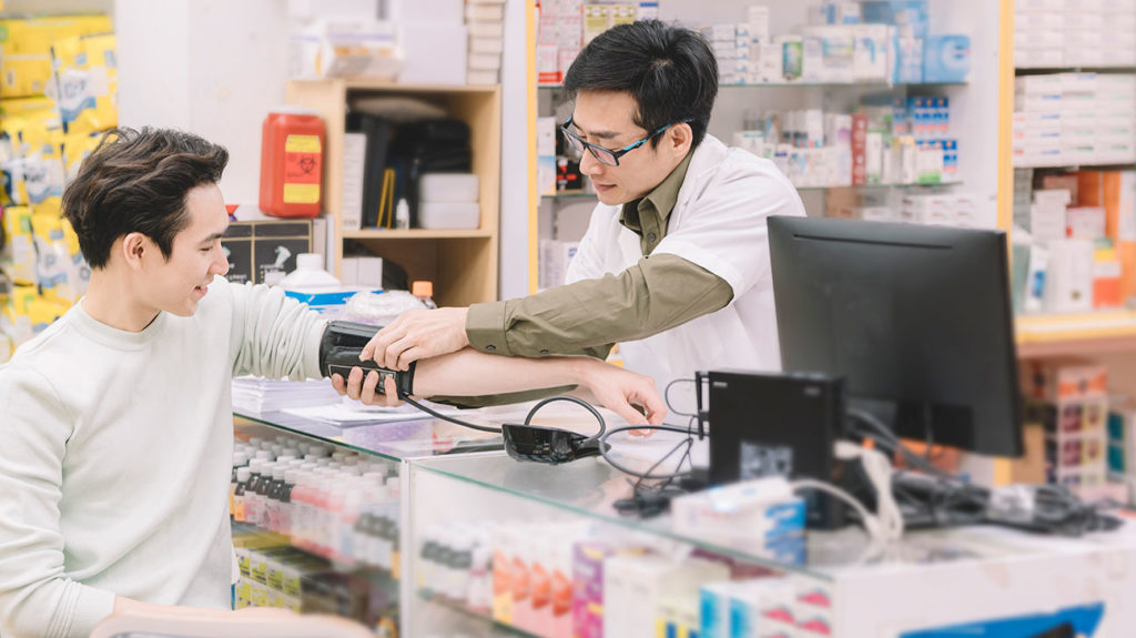A man gets his blood pressure taken at a pharmacy and considers buying supplements to lower blood pressure.