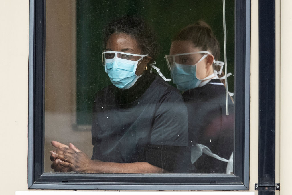 two nurses wearing face masks looking out the window