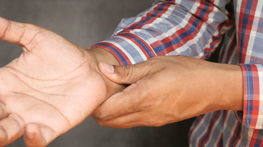 A man massages a pinched nerve in the arm.