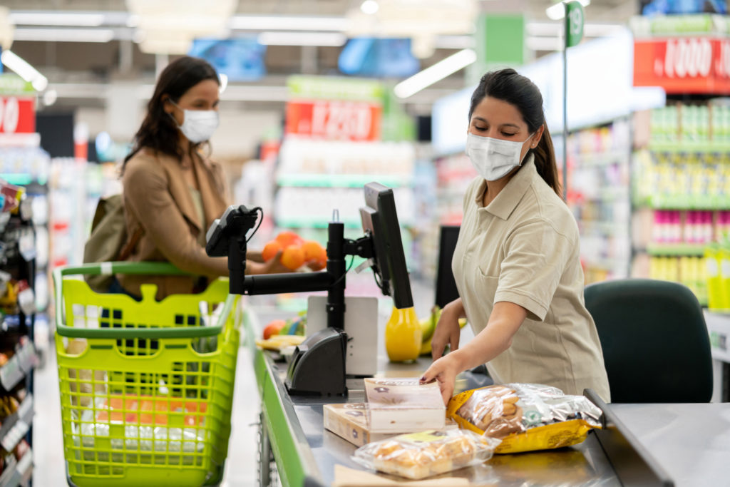Cashier scanning products at a grocery store wearing a facemask
