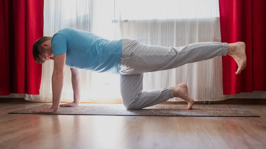 a man doing a bird dog as part of his routine of ower back stretches