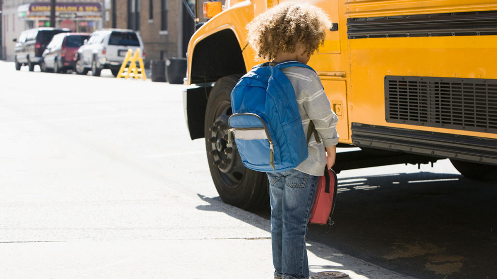 A child looks down in front of a school bus and may be exhibiting symptoms of anxiety in children.