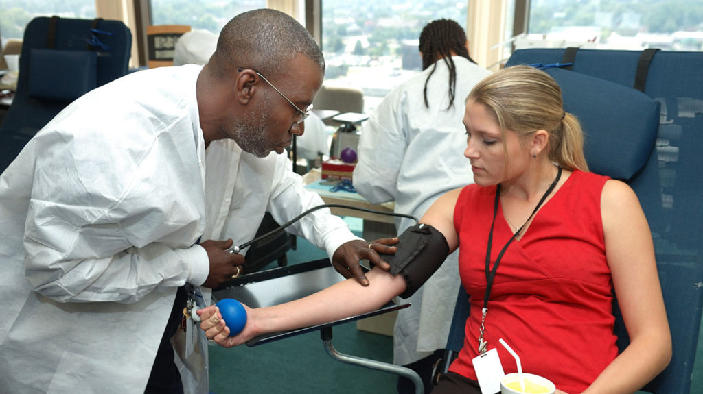 A woman talks to a doctor about blood donation facts while donating blood.