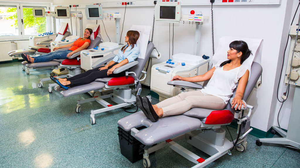 Women at a blood bank discuss how often can you donate blood while waiting to donate.