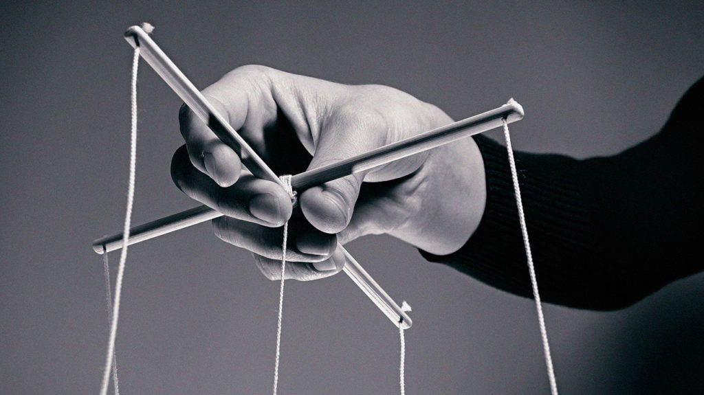 hands holding puppet strings used to represent gaslighting