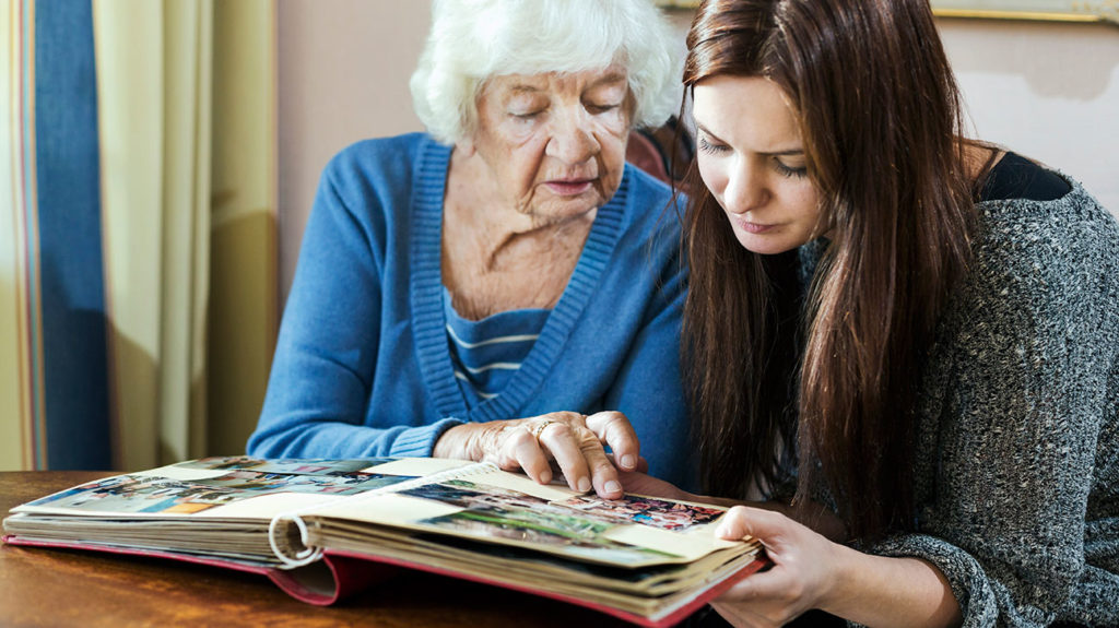 A woman with depression and memory loss looks through a scrapbook with her granddaughter.
