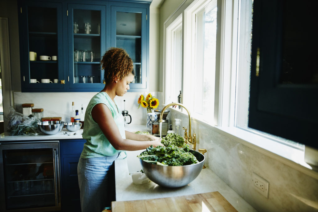 Woman washing organic kale in kitchen sink