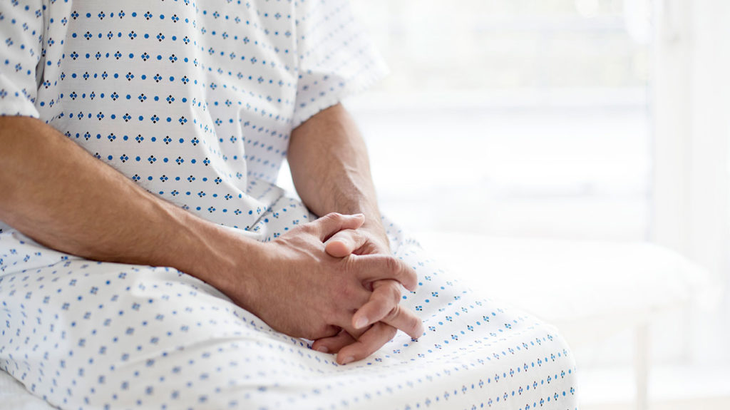 A man in a gown sits, waiting for his cystoscopy.