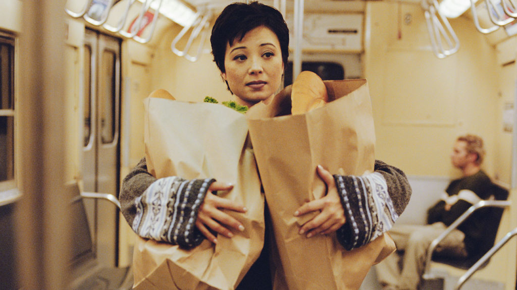 A woman who lives in one of the many food deserts takes a subway home from the grocery store.
