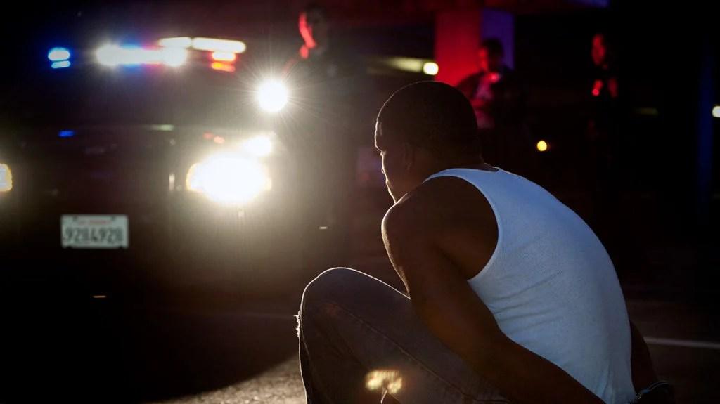 Personne noire en premier plan, voiture de police en arrière-plan