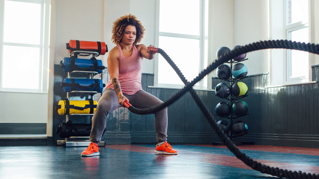 a woman with a mesomorph body type doing a workout with ropes