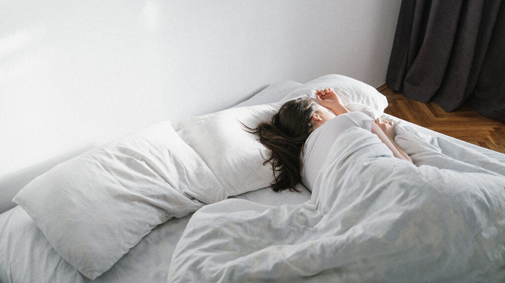 A woman is seen in bed, oversleeping.