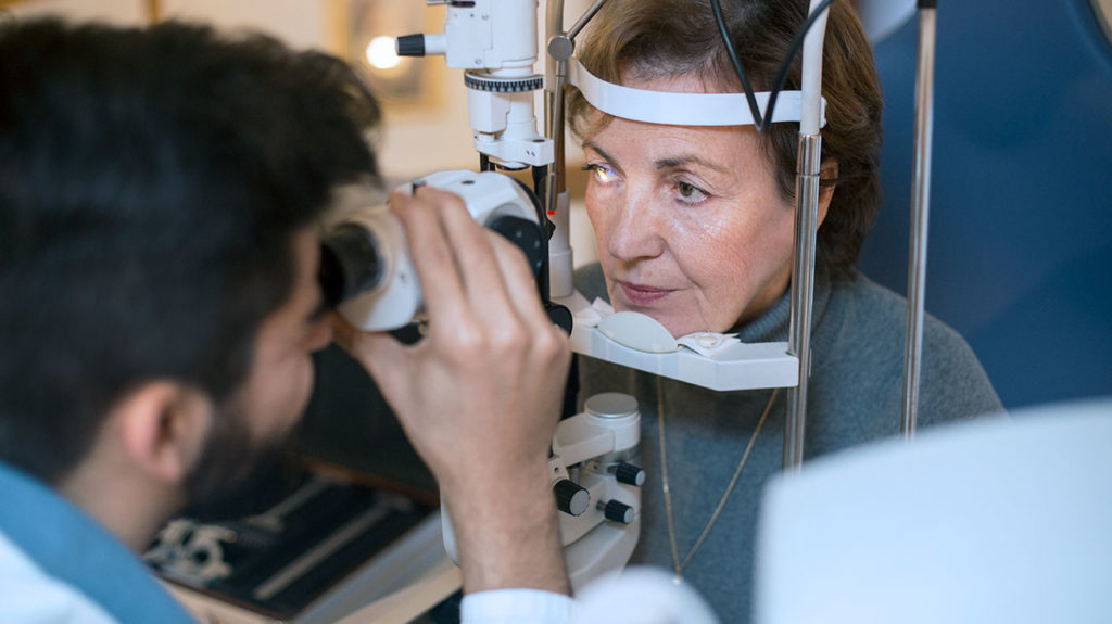 An eye doctor conducts a glaucoma screening for a patient with Medicare.