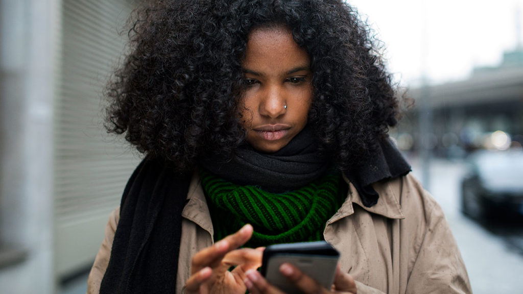 A Black woman reads the news on her phone, which can trigger racial trauma.
