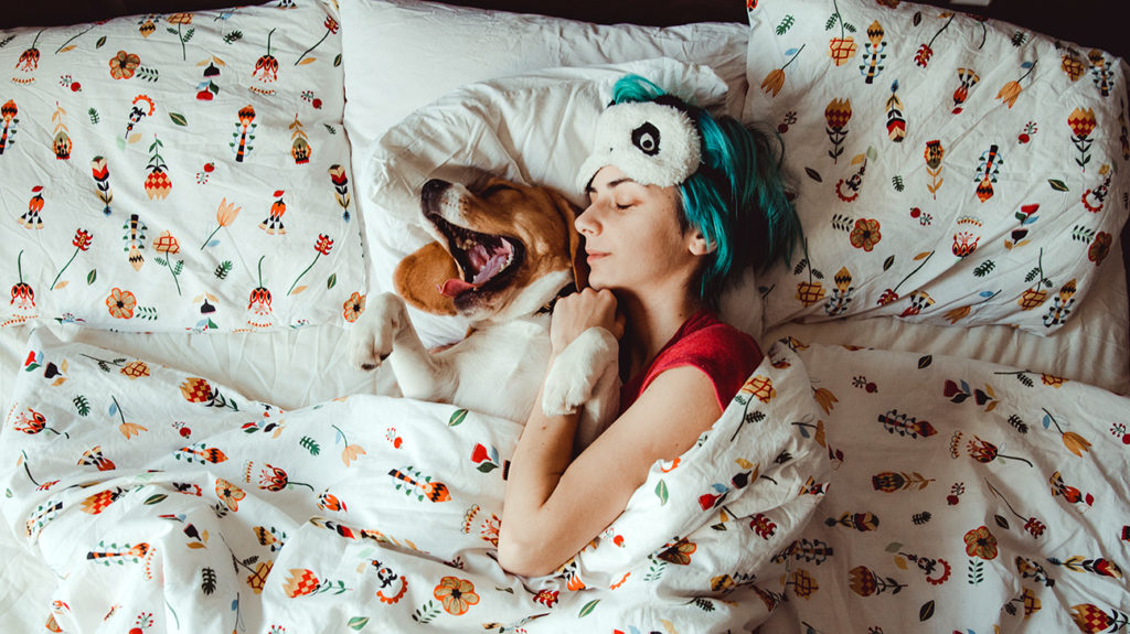 a woman sleeping in bed with a dog