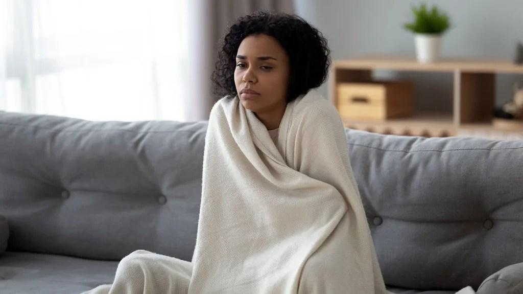 一个女人经历症状,包括寒意,可能是焦虑症状与Covid-19症状。