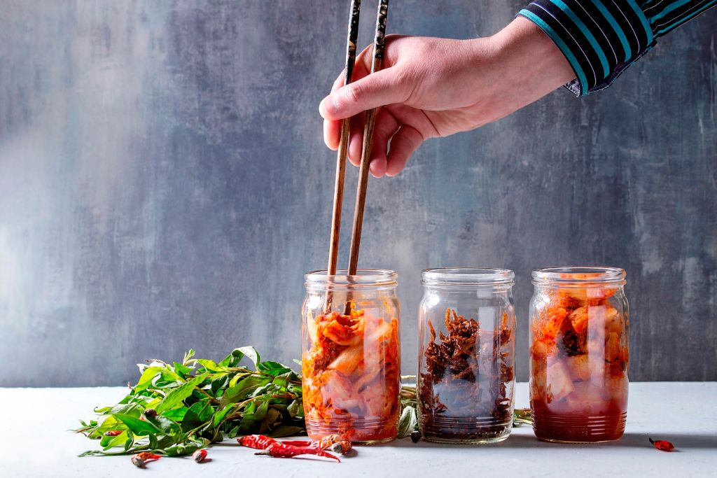 close up of hand reaching in jar for kimchi