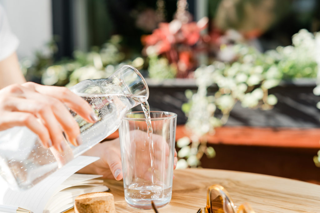 personne versant de l'eau dans un verre