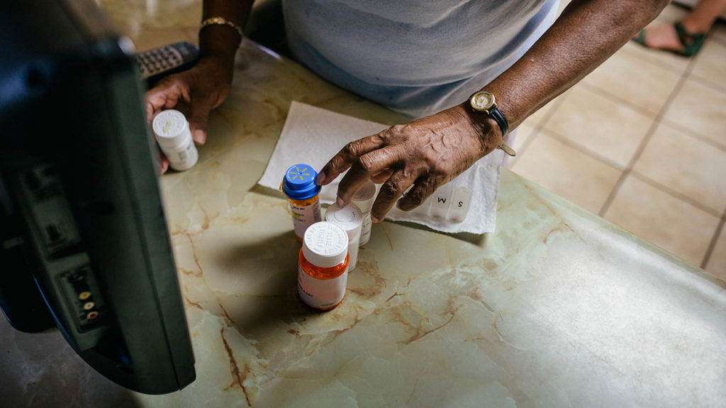 a woman sorting medicine that she has covered by medicare part c that is not going away