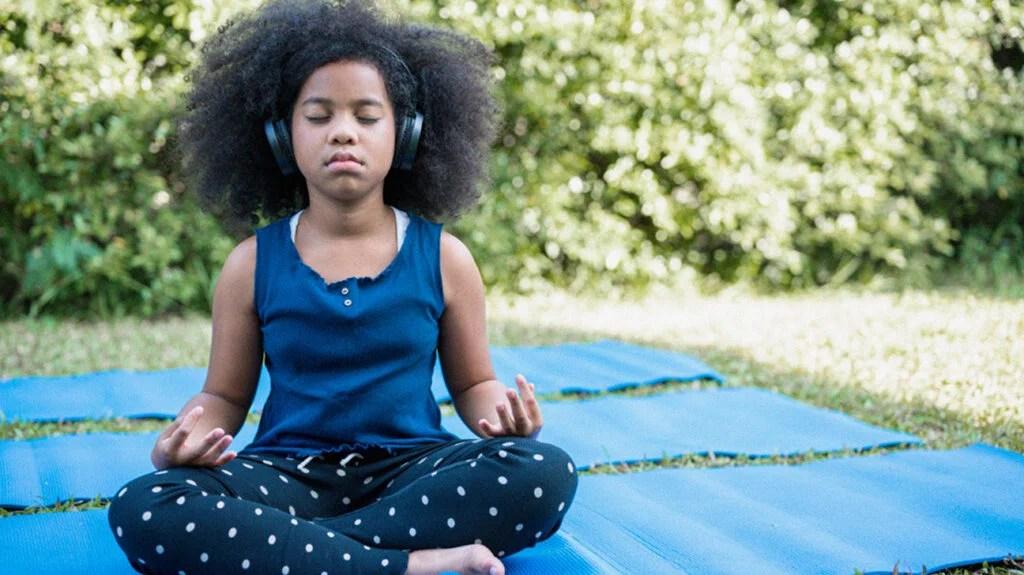 一个小女孩坐在瑜伽垫上,为孩子们打坐