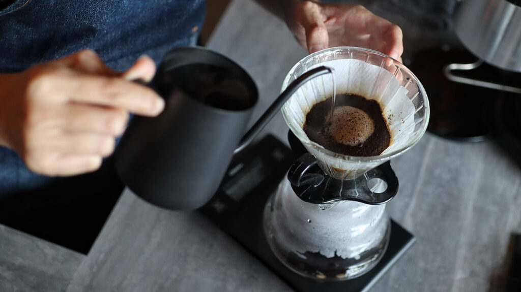 A person wonders does coffee raise blood pressure as they prepare a pour over cup of coffee.