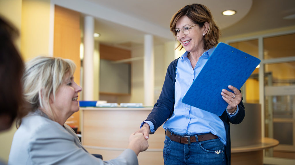 a doctor shaking hands with and talking to a woman about do i qualify for medicare savings program