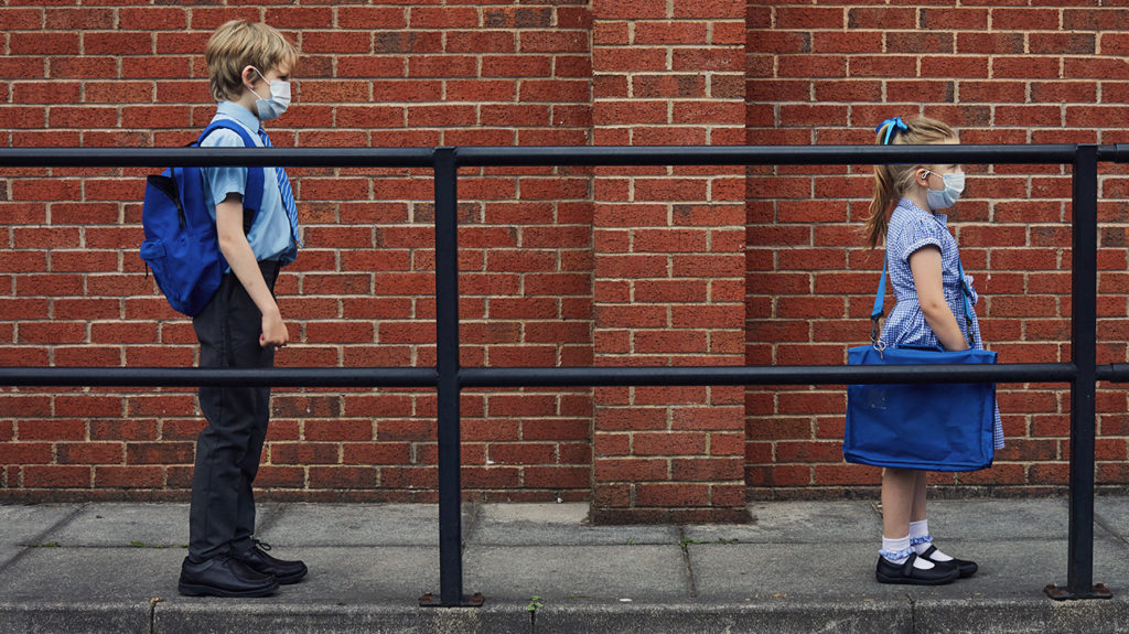 two children wearing face masks as they queue in a socially distanced manner outside a school