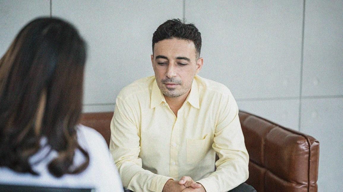 一个男人坐着与EAP辅导员交谈