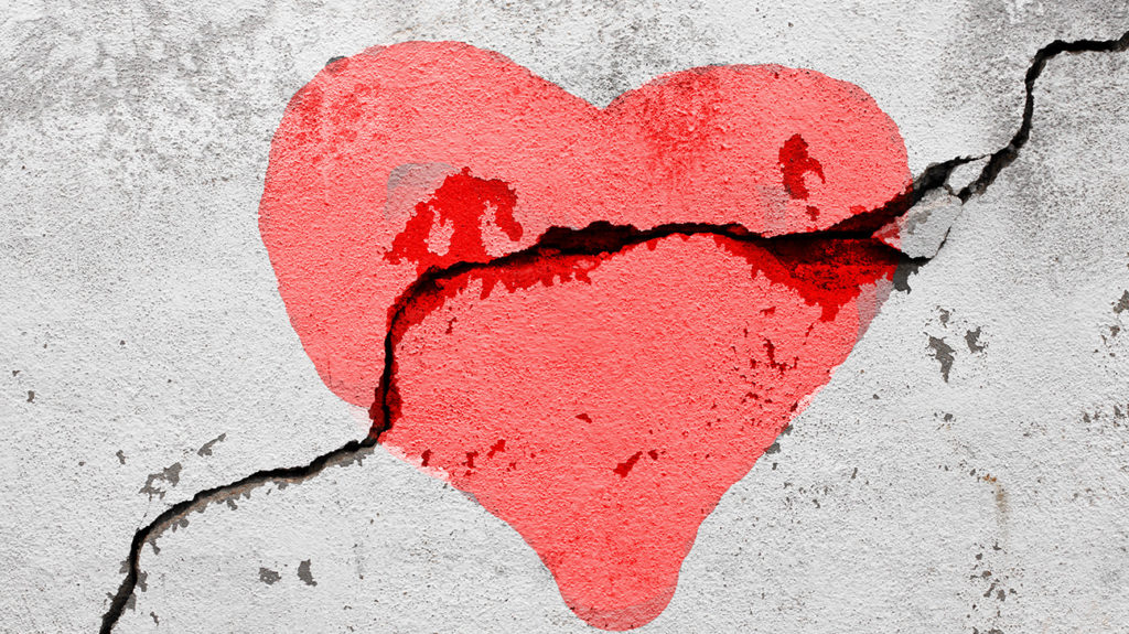 a crack over a wall with a painted heart on it used to represent broken heart syndrome