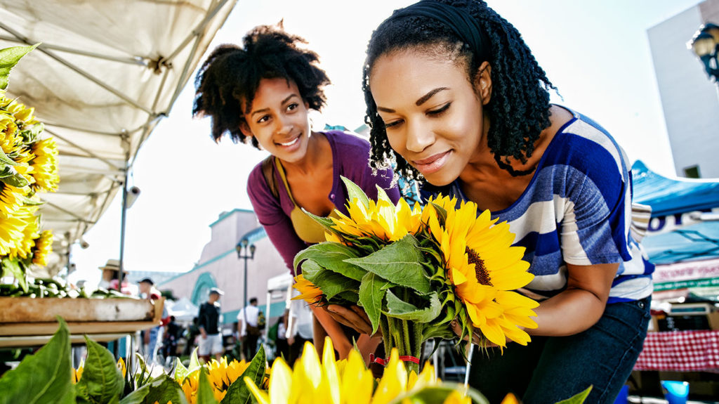A woman buys sunflowers at a farmers market, which increases her exposure to light, and is a way how to increase serotonin.