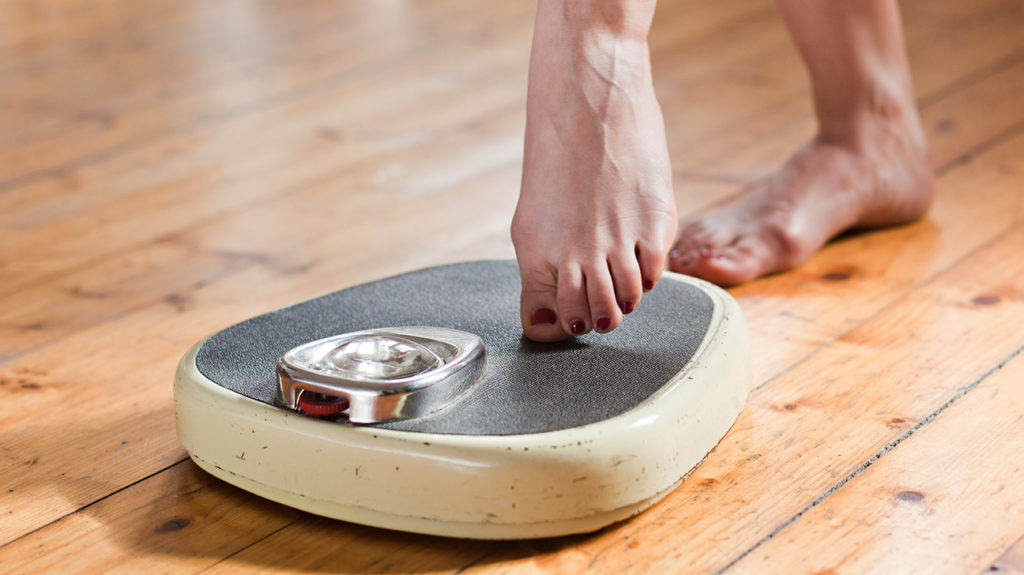 a woman stepping on scales