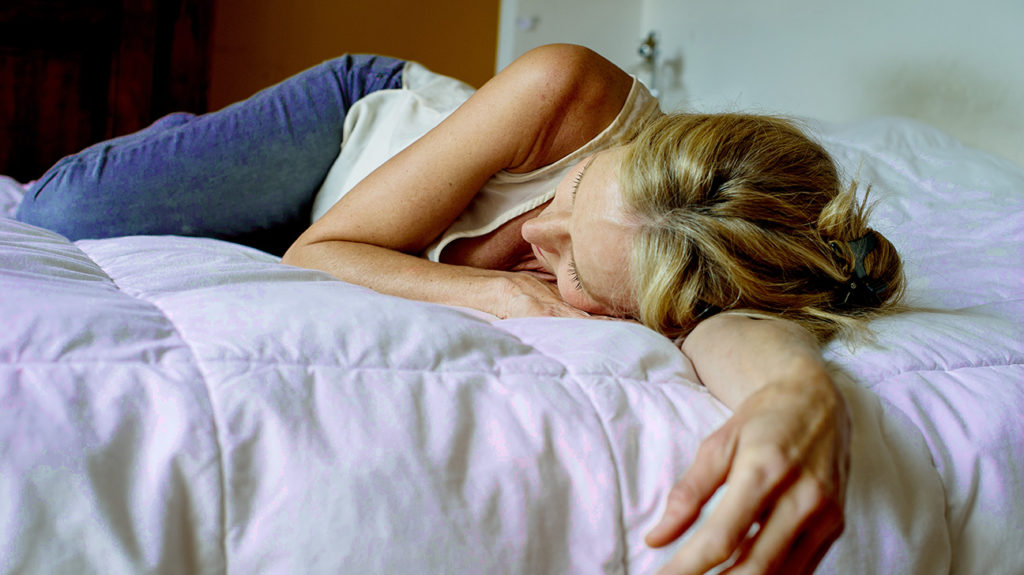 a woman lying on a bed because feeling tired is a side effect of her depression