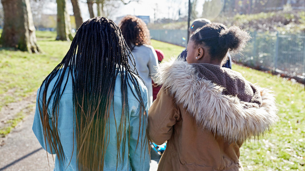 a group of black girls walking who may experience anxiety because of exposure to racism