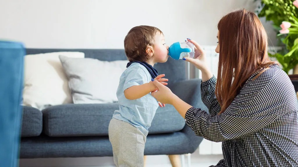 A mother gives her child some water, which could act as congestion relief for toddlers.