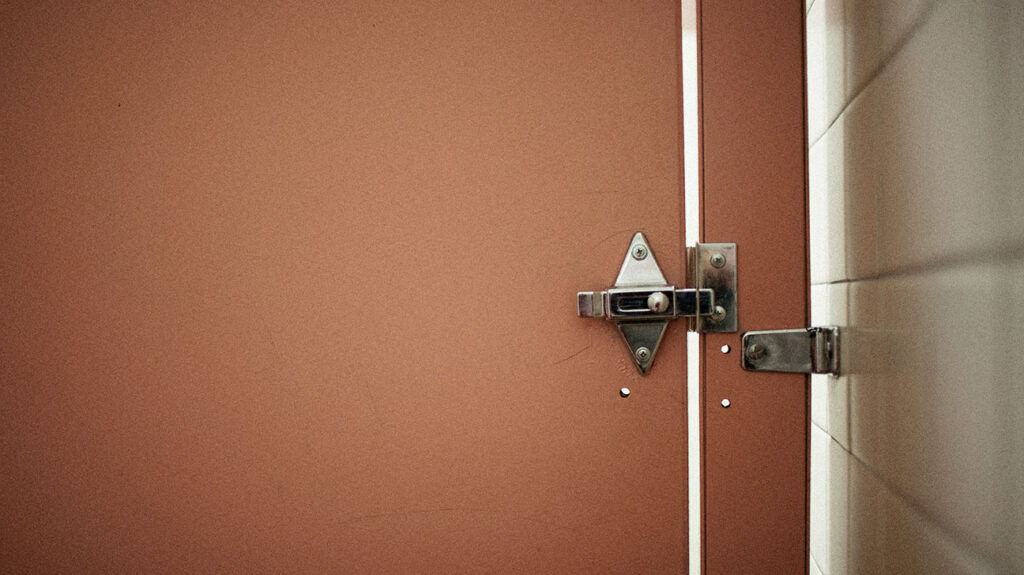 The interior of a public restroom door to accompany an article about blood in stool.