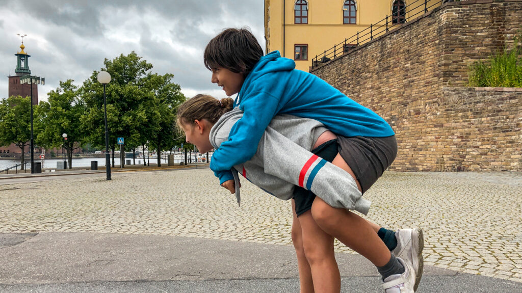 A girl, who is roughly 12, carrying a boy, who is also roughly 12, on piggyback in a city.