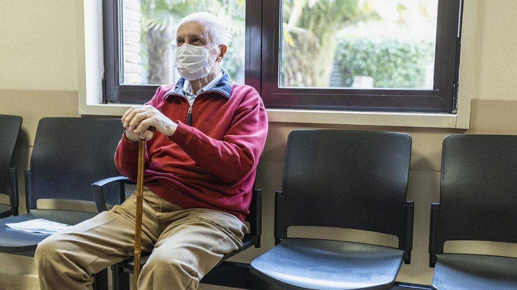 "A senior white man with breathing problems sits in the waiting room at a hospital to accompany the article, ""COVID-19: Breathing problems are the most common reason for returning to the hospital."""