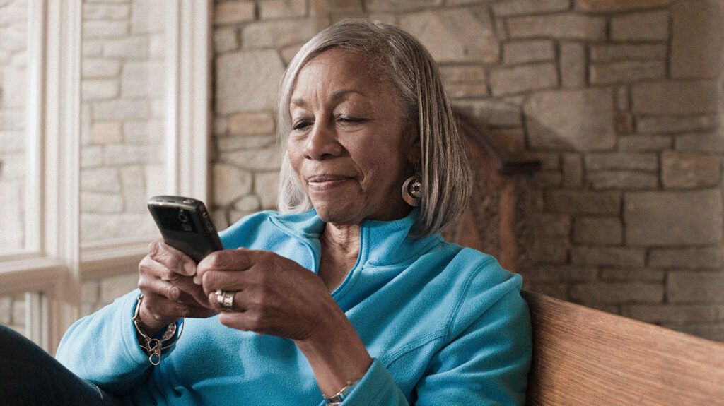 Older female adult using a mobile device to look for the medicare phone number