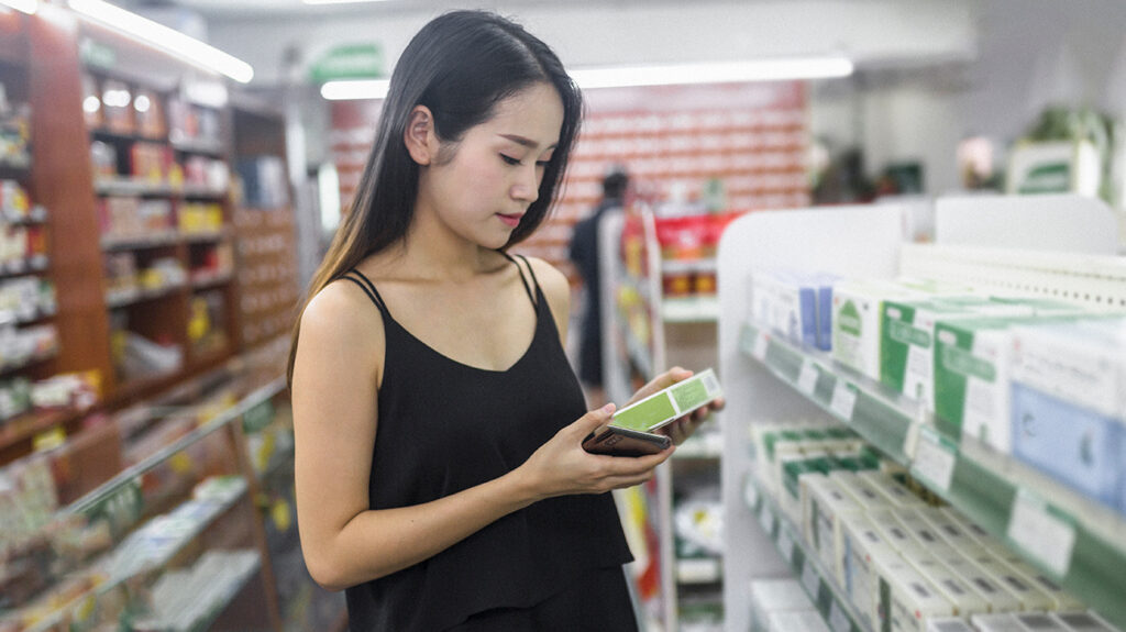 An Asian woman purchases acid reflux medicine.